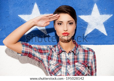 Salute! Fashionable young short hair woman in casual shirt posing against American flag background  - stock photo