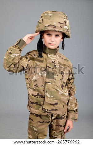 Saluting soldier. Young boy dressed like a soldier isolated on gray background - stock photo