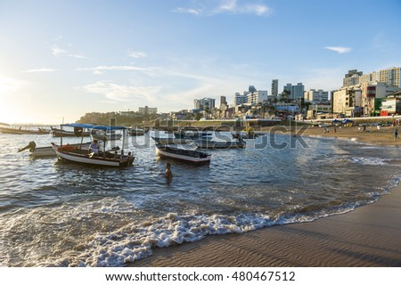 SALVADOR, BRAZIL - FEBRUARY 20, 2016: Brazilians maneuver traditional boats along the shallow waters at the shore of the fishing village of Rio Vermelho.