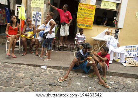 SALVADOR, BRAZIL - FEBRUARY 27, 2014: Young Brazilians socialise on the cobblestone street of Pelhourinho as preparations gear up for Carnaval celebrations. - stock photo