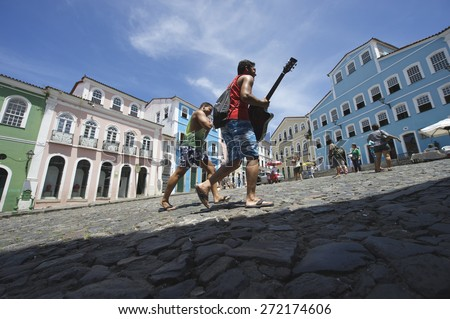 SALVADOR, BRAZIL - MARCH 12, 2015: Musician carrying guitar passes in front of colorful colonial architecture on a broad cobblestone hill in the historic city center of Pelourinho.  - stock photo