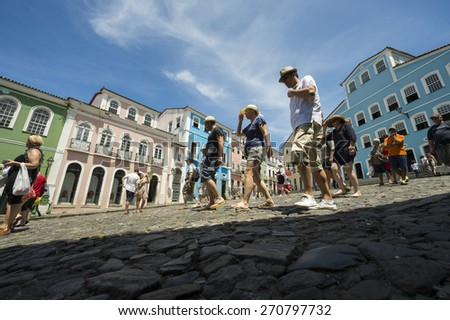 SALVADOR, BRAZIL - MARCH 12, 2015: Pedestrians pass in front of colorful colonial architecture on a broad cobblestone hill in the historic city center of Pelourinho.  - stock photo