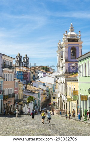 SALVADOR, BRAZIL - MARCH 12, 2015: Tourists walk in a plaza surrounded by colonial buildings in the historic district of Pelourinho. - stock photo