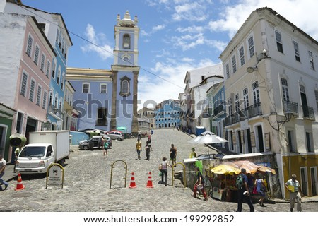 SALVADOR, BRAZIL - OCTOBER 15, 2013: Tourists and locals mix on the cobblestone streets in front of the colonial buildings of Pelourinho, the historic district.  - stock photo