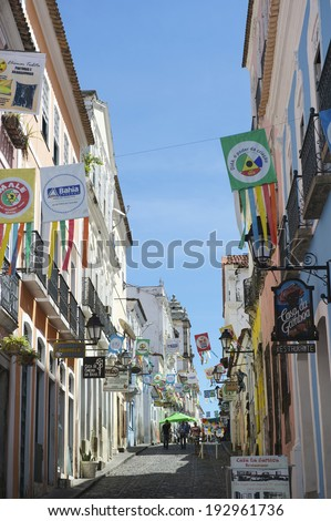 SALVADOR, BRAZIL - OCTOBER 15, 2013: Visitors walk along the cobblestone streets of the colorful historic center of Pelourinho. - stock photo