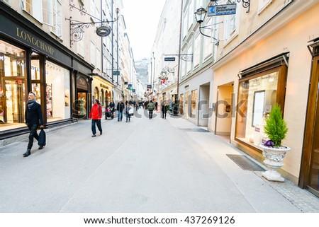 SALZBURG,AUSTRIA - 11 MARCH 2016: Back view of tourists walking along european street with different shops in Salzburg, Austria - stock photo