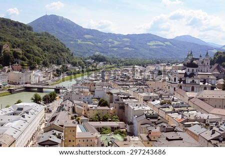 Salzburg cityscape - the Salzach river flows beneath the Staatsbruecke bridge; Salzburg Cathedral and Collegiate Church stand in the historic Old Town. The Gaisberg mountain stands in the background - stock photo