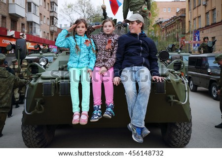 SAMARA - MAY, 6, 2015: Boy and two girls (with model releases) sitting on armored vehicle in Samara during military celebration. Red Square is not affected by military equipment on parade May 9th - stock photo