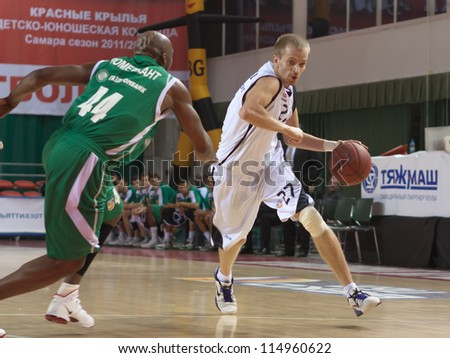 SAMARA, RUSSIA - APRIL 17: Alexey Surovtsev of BC Krasnye Krylia with ball tries to go past a BC UNICS player on April 17, 2012 in Samara, Russia.