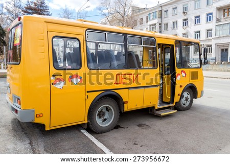 """SAMARA, RUSSIA - APRIL 26, 2015: Public school bus parked up in the street wait to collect school children. Text on russian: """"Children"""" - stock photo"""
