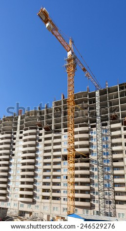 SAMARA, RUSSIA - APRIL 13, 2014:Tall apartment buildings under construction with crane against a blue sky background - stock photo