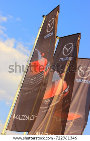 Samara, Russia - August 20, 2016. festive flags with the emblem of car MAZDA is developing the wind against the blue sky, about autofocus car sales