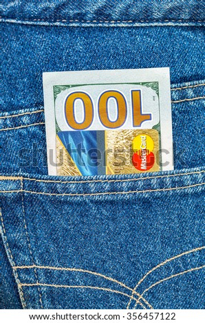 SAMARA, RUSSIA - DECEMBER 23, 2015: Credit card MasterCard with US dollars sticking out of the back jeans pocket - stock photo
