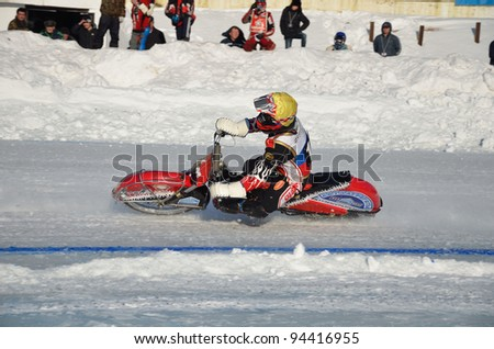 SAMARA, RUSSIA - JANUARY 29: Racing on ice, the unknown driver of a motorcycle with spikes rotates with a large slope on one knee ice speedway Championship January 29, 2012 in Samara, Russia
