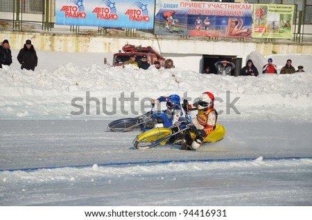 SAMARA, RUSSIA - JANUARY 29: Racing on ice, two unknown driver on a motorcycle with spikes rotates with a large slope on one knee on the ice speedway Championship January 29, 2012 in Samara, Russia