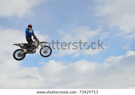 SAMARA, RUSSIA - MARCH 7: Rider A. Kravchuk high flight in the rack against the blue sky and clouds the Regional Winter Motocross Championship March 7, 2011 in Samara, Russia - stock photo