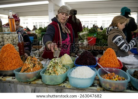 SAMARQUAND, UZBEKISTAN - MARCH 14, 2015: City grocery market.  Man sells pickled carrots and cabbage. - stock photo
