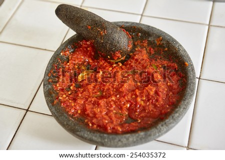Sambal, special spicy chili paste in Indonesia, making on stone mortar to be eaten with another meal - stock photo