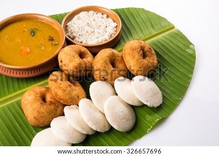 Sambar Vada & Idli with sambar, coconut chutney and red tomato chutney in earthen pots, served over green banana leaf over white background  - stock photo