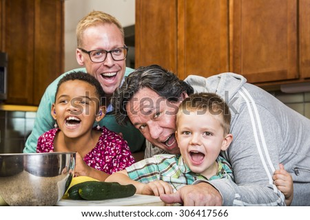 Same sex couple and kids having fun at meal time - stock photo