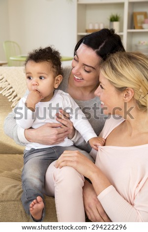 Same sex femal couple sitting with their son at home - stock photo