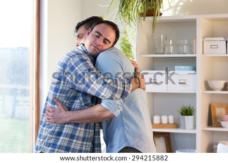 Same sex male couple embraced in a hug in their home. - stock photo