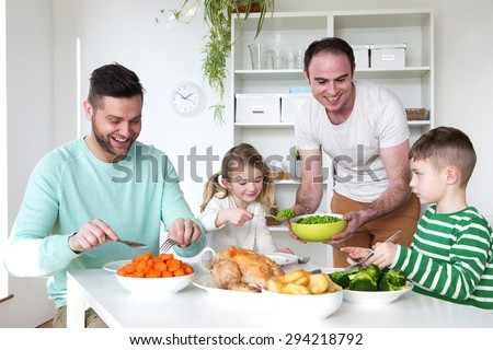 Same sex male couple smiling for the camera with their daughters at home.