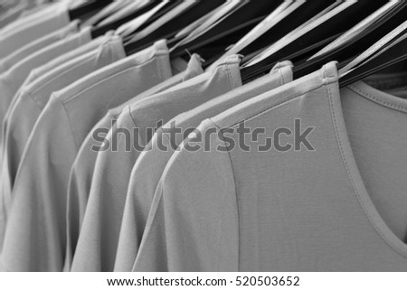 Same shirts on black hangers, grey fashion background