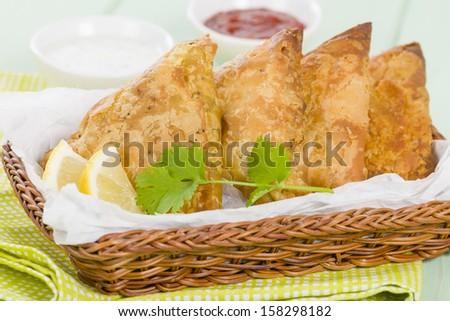Samosas - Deep fried stuffed pasties served with lemon wedges, chili sauce and yoghurt raita. - stock photo