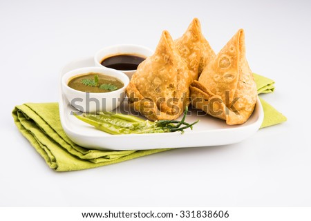 samosas - Indian deep fried snack, served with chutney and fried green chilly, in white plate, isolated on white background  - stock photo