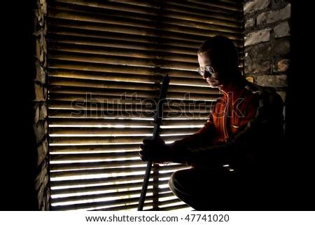 samurai undergrounder with sword near persiennes - stock photo