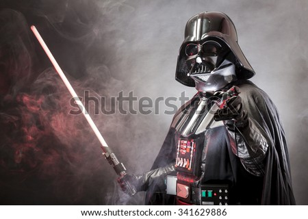 SAN BENEDETTO DEL TRONTO, ITALY. MAY 16, 2015. Portrait of Darth Vader costume replica with grab hand and  sword . Darth Vader is a fictional character of Star Wars saga.  Red grazing light and smoke - stock photo