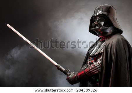 SAN BENEDETTO DEL TRONTO, ITALY. MAY 16, 2015. Portrait of Darth Vader costume replica with  his sword . Darth Vader is a fictional character of Star Wars saga.  Red grazing light and smoke - stock photo