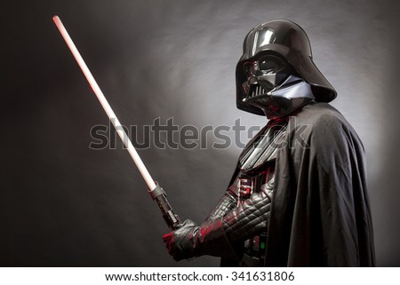 SAN BENEDETTO DEL TRONTO, ITALY. MAY 16, 2015. Portrait of Darth Vader costume replica with his sword . Darth Vader is a fictional character of Star Wars saga.  Black background - stock photo