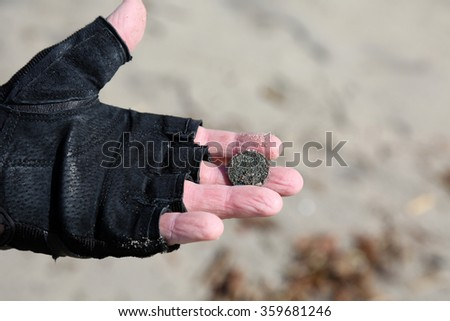 San Clemente CA Jan. 7 2016: A man uses his Metal Detector as he sifts through the sand after the Godzilla El Nino of 2016. Here he shows a Quarter he recently found buried in the sand. - stock photo