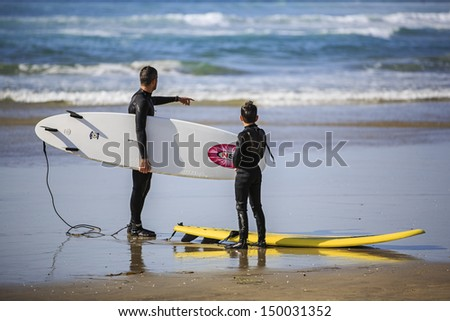 SAN DIEGO, CALIFORNIA - MARCH 31: Two unidentified surfers having conversation on March 31, 2013 in La Jolla Shore beach, San Diego, CA, USA. La Jolla Shore beach is a very famous surfing place in San Diego, CA. - stock photo
