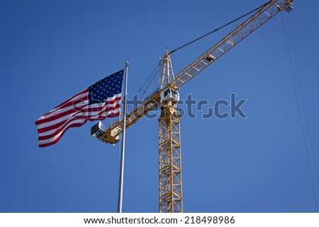 SAN DIEGO, CALIFORNIA, SEPTEMBER 10, 2014: A crane operating at a construction site with the American Flag in the foreground, in San Diego, California. - stock photo