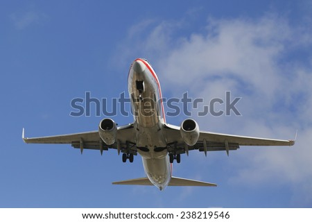 SAN DIEGO, CALIFORNIA - SEPTEMBER 27: American Airlines jet descending for landing San Diego International Airport on September 27, 2014. In 2013 the American Airlines fleet consists of 621 aircraft  - stock photo