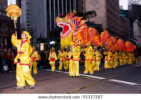 SAN FRANCISCO, CA - FEBRUARY 11: Unidentified children dancing with a dragon during the Chinese New Year Parade in San Francisco. It is the largest Asian event in North America. February 11, 2012 - stock photo