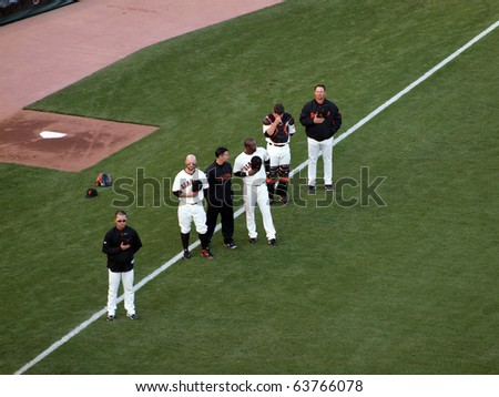 SAN FRANCISCO, CA - OCTOBER 20: Giants vs. Phillies: Giants Players stand with hats removed during National anthem before the start of game four NLCS 2010 October 20, 2010 AT&T Park San Francisco. - stock photo