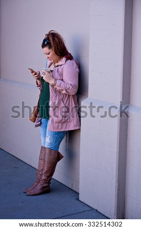 SAN FRANCISCO, CA - October 10, 2015 - Woman standing, leaning against a wall looking at her phone with a drink in her hand.