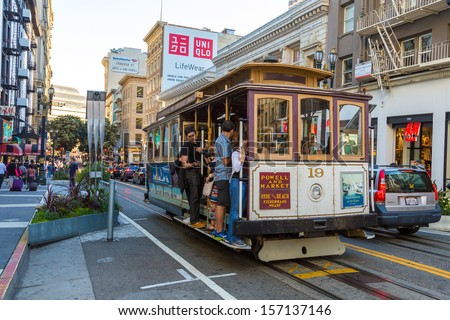 SAN FRANCISCO, CA - SEP 20: Passengers enjoy a ride in a cable car on September 20, 2013 in San Francisco. It is the oldest mechanical public transport in San Francisco which is in service since 1873. - stock photo
