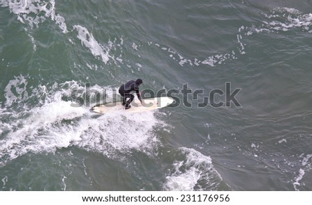 SAN FRANCISCO, CA, USA - APRIL 2010: Aerial View of surfer in wet suit riding a wave. San Francisco Bay, California, USA