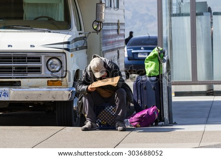 San Francisco, California - May 11 : Homeless man on a sidewalk with a sign asking people for help, May 11 2015 San Francisco, California. - stock photo