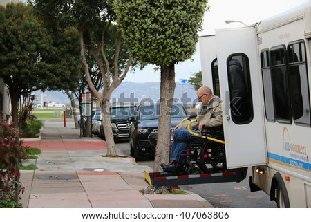 San Francisco, California, USA - December 24, 2015: Old man in a wheelchair is assisted to get off a van using a lift.