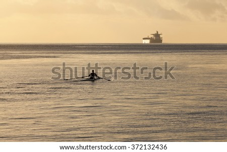 San Francisco, California USA - November 19, 2011: A woman in a single scull boat practicing rowing on the San Francisco Bay by predawn morning light - stock photo