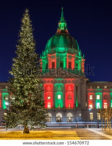 San Francisco City Hall in red and green light and a Christmas tree in front. - stock photo