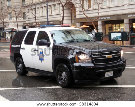 SAN FRANCISCO -  JANUARY 20: Ford Explorer SFPD cop vehicle rolls down market street during a Protest for 'House Keys, not handcuff' on rainy day.   January 20, 2010 San Francisco California. - stock photo