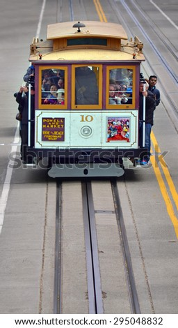 SAN FRANCISCO - MAY 19 2015:Passengers riding on cable car on steep hill in San Francisco, CA.By 1979, the cable car system had become unsafe, and closed for 7 months for urgently needed repairs - stock photo
