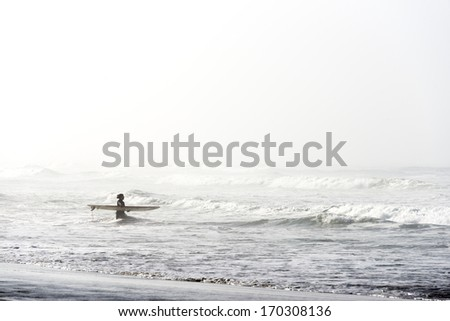 SAN FRANCISCO - OCTOBER 29: A late season surfer heads to the cold water with her board surrounded by the morning mist, in San Francisco, California, on October 29, 2012.